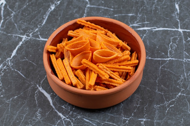 Assortimento di patatine speziate in ciotola di ceramica.