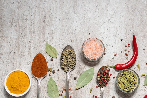 Assortment of spices and herbs on marble background top view.