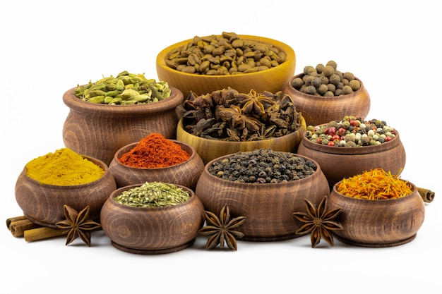 An assortment of spices and seasonings in wooden bowls isolated on a white background.