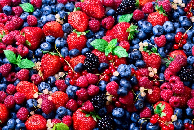 Assortment of strawberry, blueberry, currant, mint leaves. summer berries background with copy space for your text. vegan, vegetarian concept.