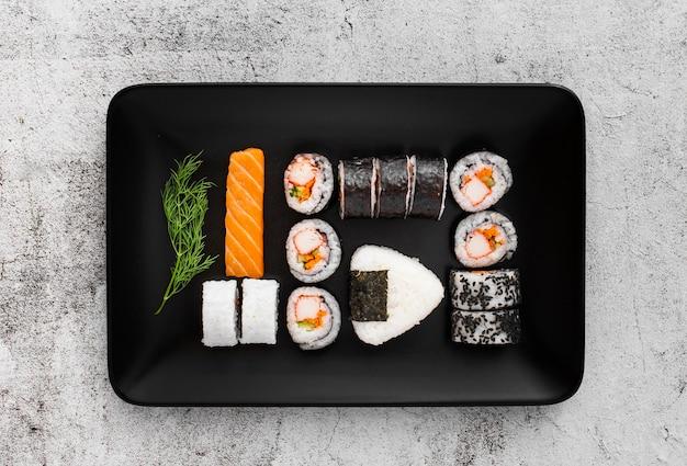 Assortment of sushi on black rectangular plate