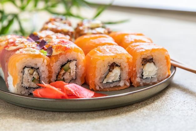 Assortment of sushi rolls served with ginger sticks on ceramic plate sushi menu japanese food