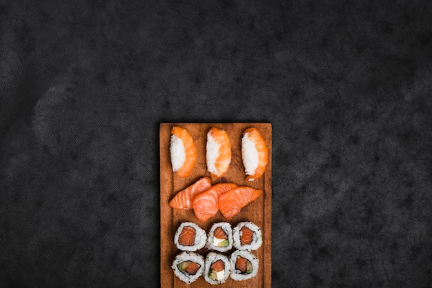 Assortment of sushi on wooden tray against black texture backdrop