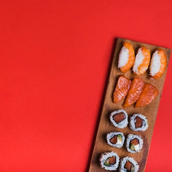Assortment of sushi on wooden tray against red backdrop with copy space for writing the text