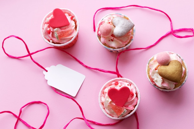Assortment of tasty cakes on pink background.