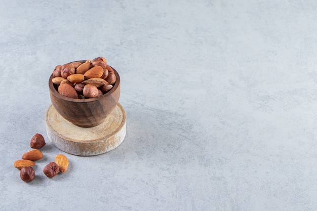 Assortment of tasty dried fruits and nuts in wooden bowl.