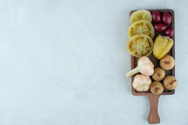 Assortment of tasty fermented vegetables on wooden board.