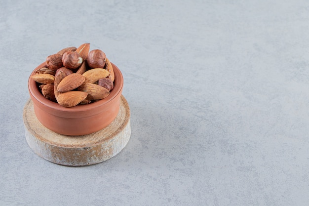 Assortment of tasty organic nuts in bowl on stone background.