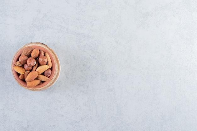 Assortimento di gustose noci organiche in ciotola su fondo di pietra.