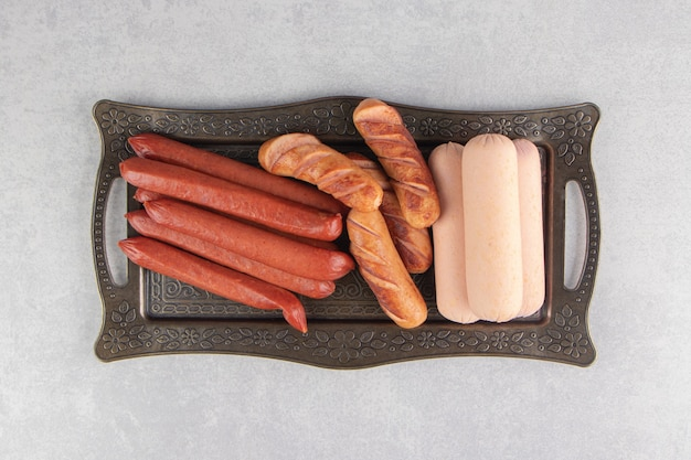 Assortimento di gustose salsicce su vassoio di metallo.