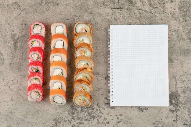 Assortment of tasty sushi rolls and blank notebook on marble background