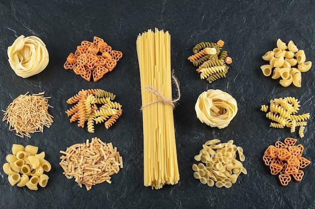 Assortment of uncooked pasta on black.