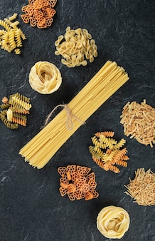 Assortment of uncooked pasta on dark.
