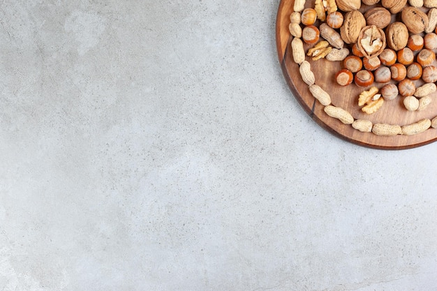 An assortment of various nut types on wooden board on marble background.