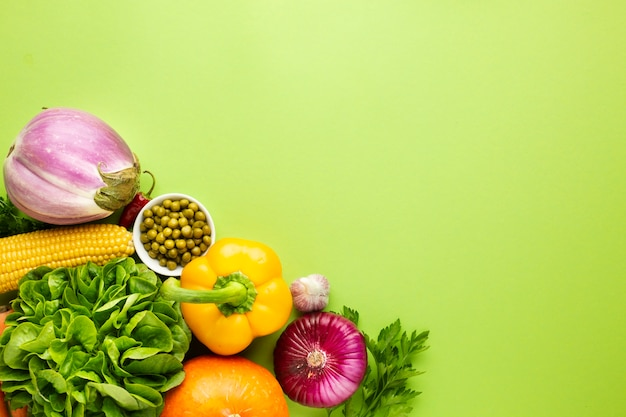 Assortment of veggies on green background with copy space