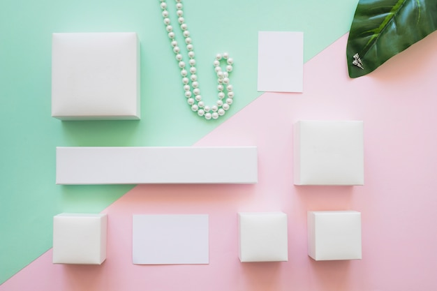 Assortment of white boxes, necklace and earrings with adhesive note on background