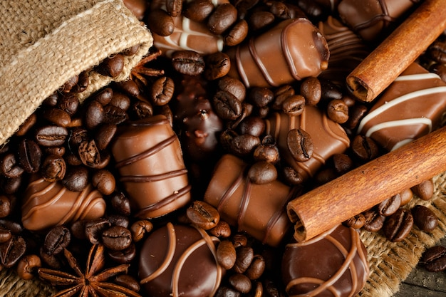 Assortment of white, dark, and milk chocolate. chocolate with cream, nuts, almonds, hazelnuts and cinnamon with coffee beans. sweet food and no diet concept.