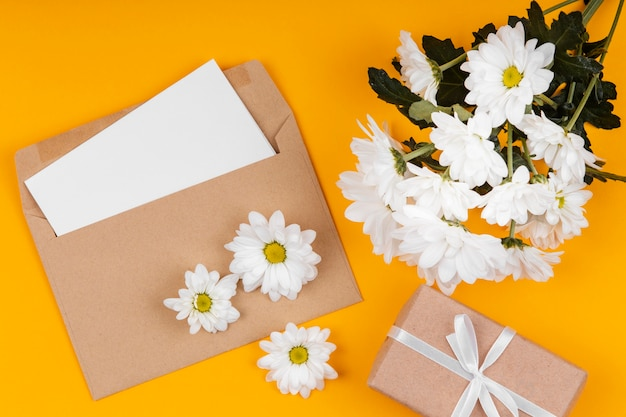 Assortment of white flowers with envelope and wrapped gift