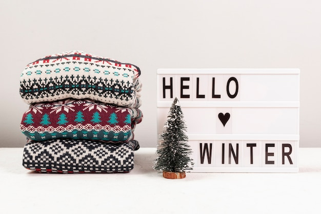 Assortment with sweaters and hello winter sign