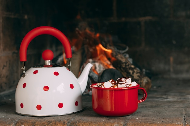 Assortment with teapot and mug near the fireplace