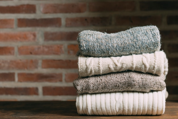 Assortment with warm clothes and brick wall