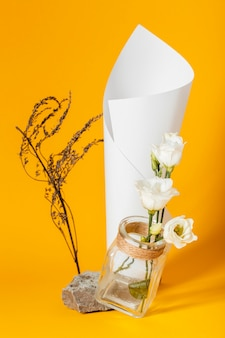Assortment with white roses in a vase with a paper cone