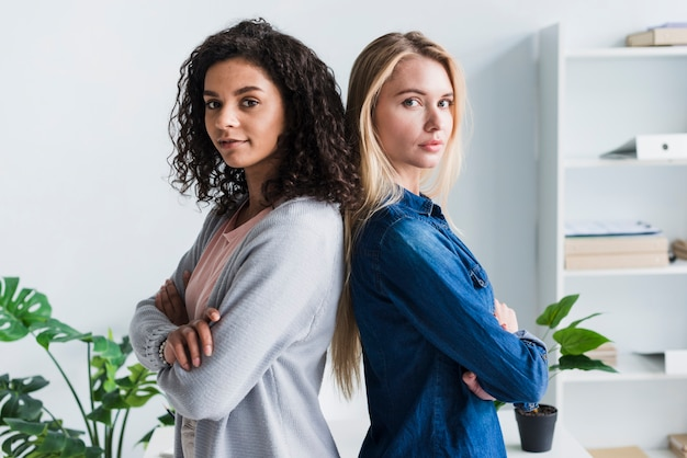 Assured ethnic and blond female office workers team