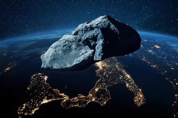 小惑星は、宇宙空間からの眺めで、黄色の街の明かりで青い惑星地球の近くを飛んでいます。宇宙の概念における危険