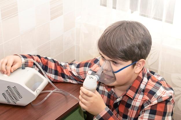 Астма у детей. мальчик вдыхает лекарство от ингалятора.