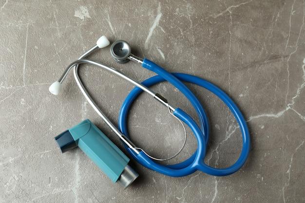 Ингалятор астмы и стетоскоп на сером текстурированном столе