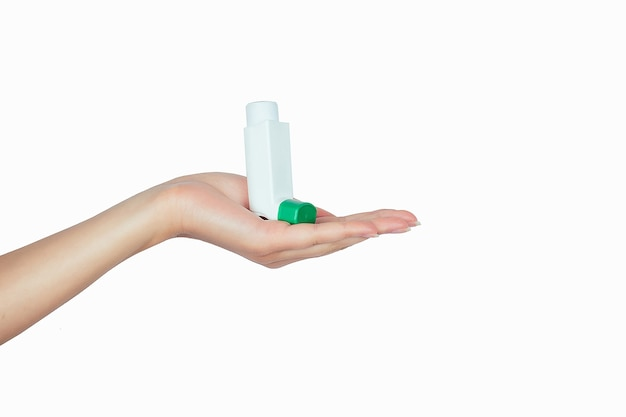 Asthma inhaler in hand on white isolate