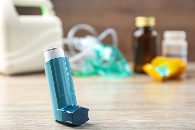 Asthma inhaler, nebuliser and medicines on wooden table