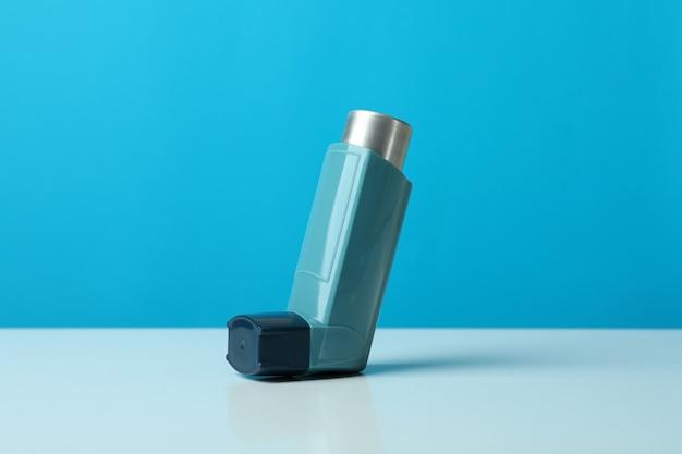Ингалятор астмы на белом столе на синем фоне