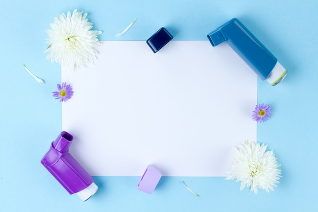Asthma inhalers and flowers on blue