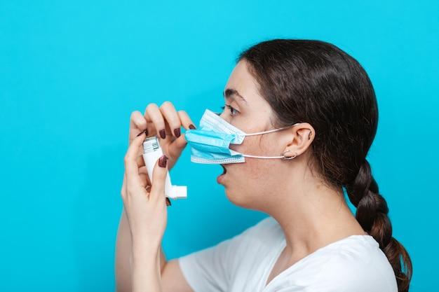 Астма. портрет молодой женщины в медицинской маске, держащей ингалятор во рту. вид сбоку.