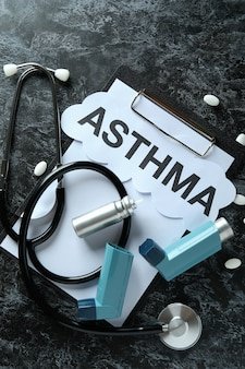 Asthma treatment accessories on black smokey table