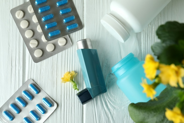 Asthma treatment accessories on white wooden table