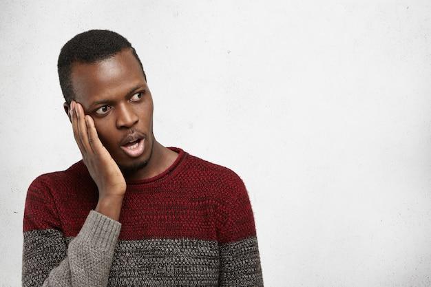 人間の感情と感情。ハンサムなショックを受けたアフリカ系アメリカ人男性が驚きとastohisnmentで頬に手を握ってカジュアルなセーターを着て、空白の白いコピースペースの壁、口を大きく開いて見て