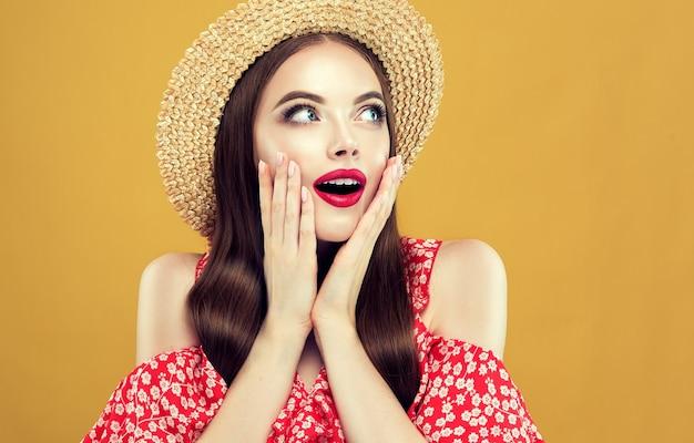 놀랍고 흥분된 젊은 장발 모델은 보이지 않는 제품 또는 물체를 옆으로 바라보고 있습니다. 가벼운 여름 가운과 밀짚 모자를 입은 여자. 그녀의 얼굴에 붉은 입술로 밝은 메이크업. 광고.
