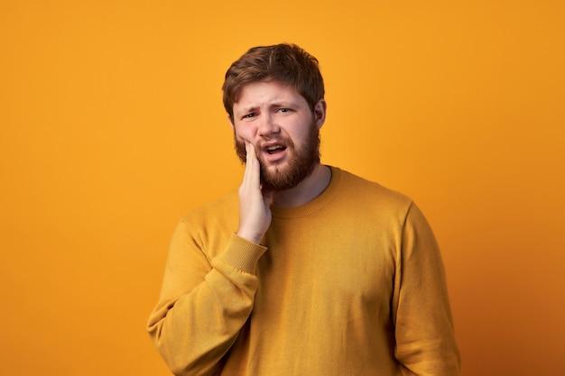Удивленный привлекательный мужчина с рыжей длинной бородой, удивляется неожиданным новостям, держит рот приоткрытым, смотрит в камеру, носит повседневную одежду и очки, позирует на фоне белой стены с пустым пространством
