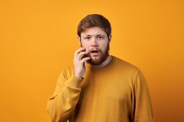 びっくりした魅力的な男性は生姜の長いあごひげを生やし、突然のニュースを不思議に思い、口を少し開いたままにします