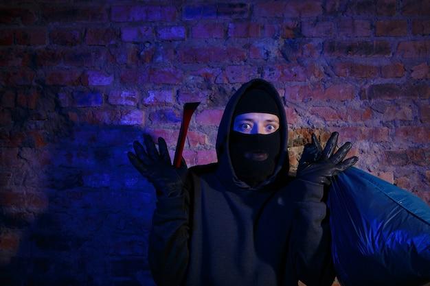 가방과 마스터 키로 벽돌 벽 근처에서 놀란 산적의 밤