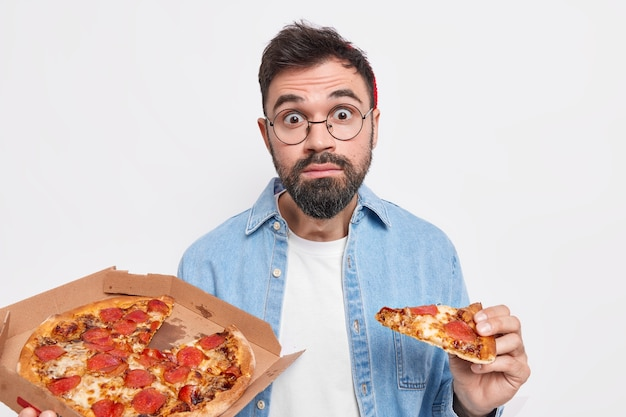 Astonished bearded adult man holds slice of pizza eats fast food has surprised expression thick beard wears casual clothes