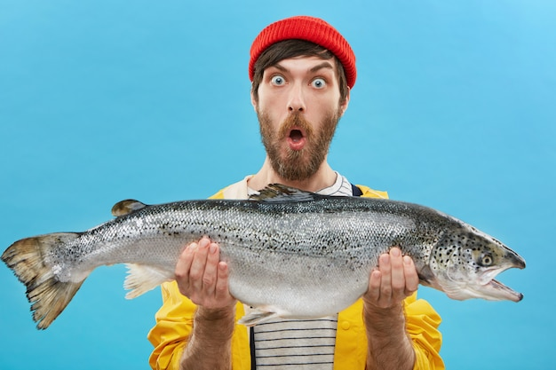 Astonished bearded fisherman dressed casually holding huge fish looking with bugged eyes and jaw dropped being shocked to catch such big trout or salmon.