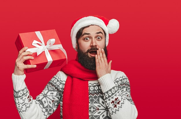 Astonished bearded hipster in sweater and santa hat