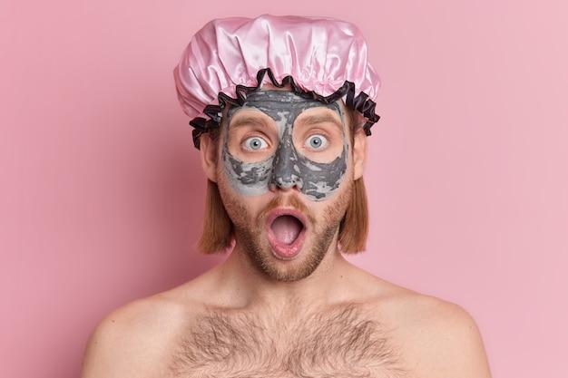 L'uomo barbuto stupito applica una maschera di argilla sul viso fisso con gli occhi spalancati, la bocca spalancata indossa un cappello da bagno protettivo.