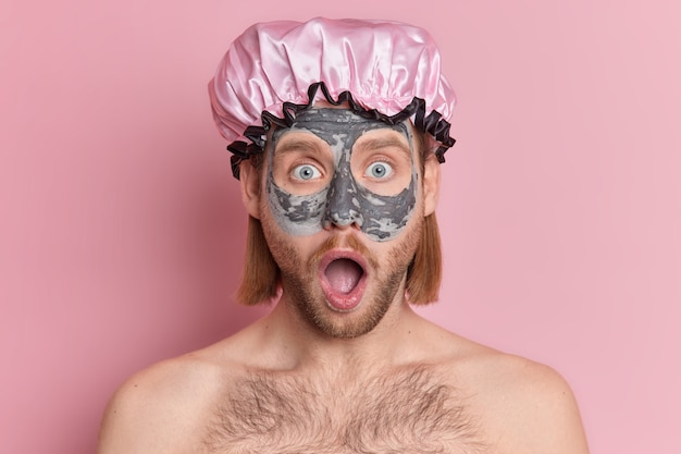 驚いたあごひげを生やした男は、目を大きく開いて顔を見つめ、保護バスの帽子をかぶって粘土マスクを適用します。