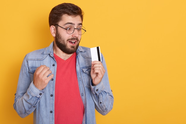 Astonished bearded man dresses denim jacket, red shirt and glasses, holding credit card in hands and looks ar card with opened mouth