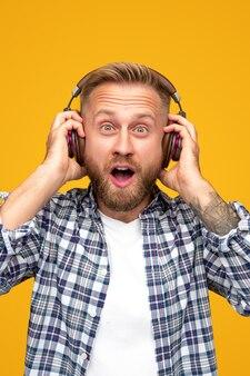 Удивленный бородатый мужчина слушает музыку