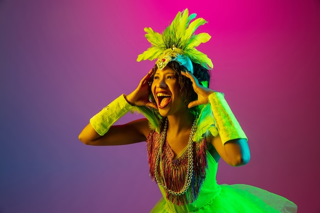 Astonished. beautiful young woman in carnival, stylish masquerade costume with feathers dancing on gradient background in neon. concept of holidays celebration, festive time, dance, party, having fun.